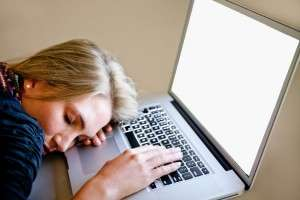 Woman with her head on her laptop, sleeping