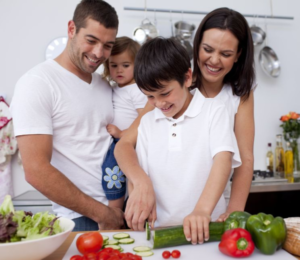 Family in the kitchen watching a young boy chopping cucumber