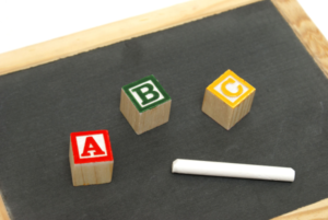 A small blackboard and piece of white chalk, with 3 cubes labelled A, B and C on it
