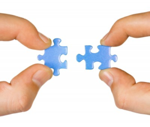 two hands holding separate interlocking jigsaw pieces