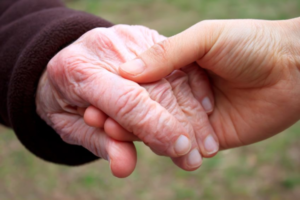 Young hand reassuringly holding an older hand