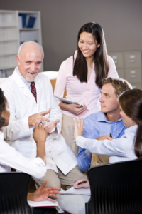 An older doctor and 4 perhaps medical students listening to him and taking notes
