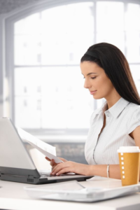 Smiling woman sat a laptop with a piece of paper in her hand, and a coffee cup on her desk