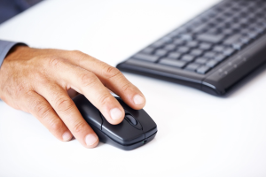 Man's hand using a computer mouse next to a keyboard