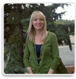 Crystal Maertens, Champ Software Marketing Specialist, standing next to a tree