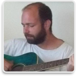 Ron Colwill, Champ Software Developer, headshot playing an acoustic guitar