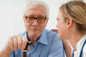 Older man with a walking stick being reassured by a nurse