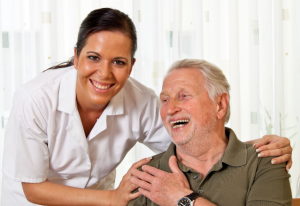 Older man being reassured by a younger nurse