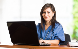 Smiling female doctor sat at a desk in front of a laptop