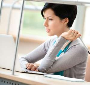 Young woman sat a laptop, concentrating, with a pen in her hand