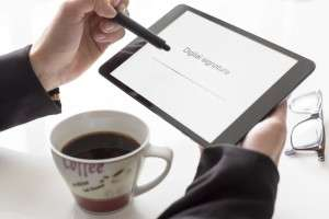 Man with a cup of coffee and glasses on the table, holding a tablet with'Digital Signature' written on the screen, and a line for the signature,
