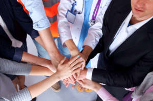 Different types of workers with their hands on top of each other, suggesting working together