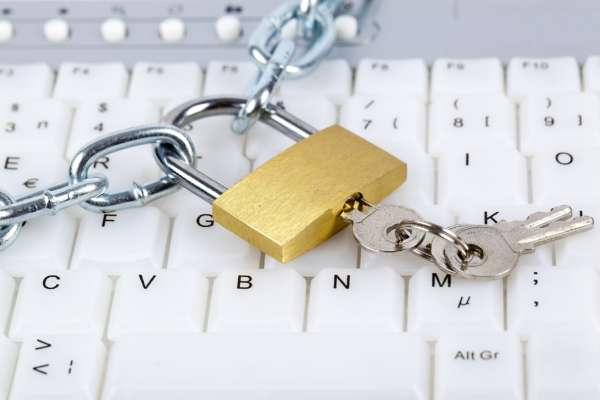 Chain, padlock and keys on a computer keyboard depicting security