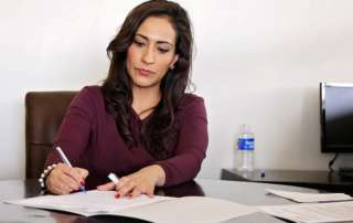Woman sat at desk writing something on a piece of paper