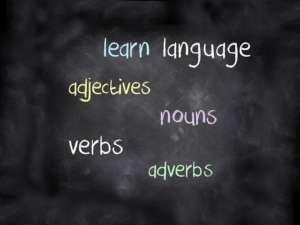 Blackboard with adjectives, nouns verbs etc written on it describing learning a language