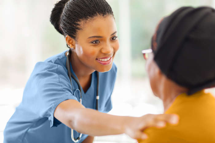 Smiling female nurse reassuring an older female patient