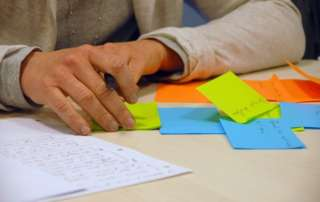 A woman holding a pen and using Post It Notes, with a notepad on her desk