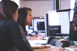 Two women sat at a desk looking at a computer screen