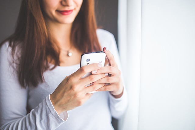 Woman looking down at cell phone her hand