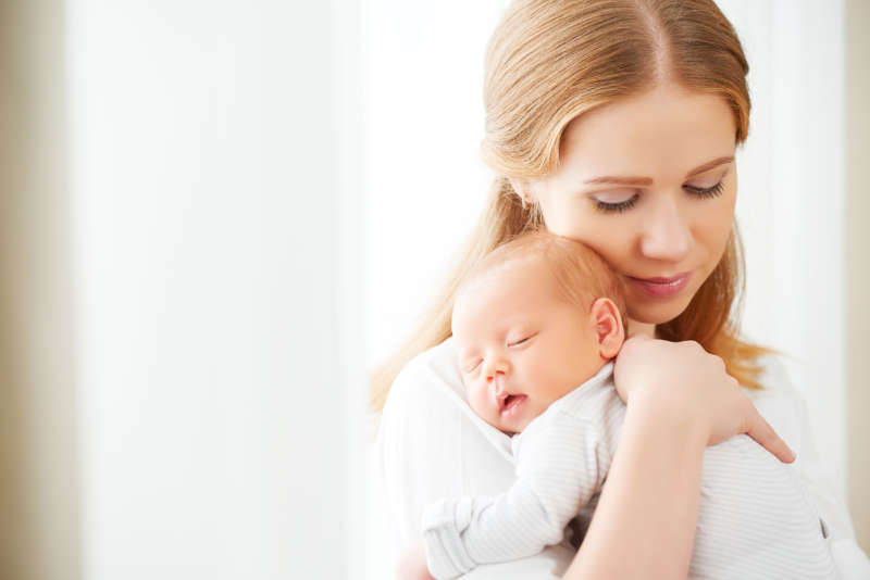 Mother holding a sleeping newborn baby on her shoulder