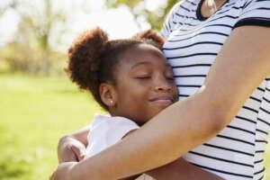 Little girl hugging safe caregiver