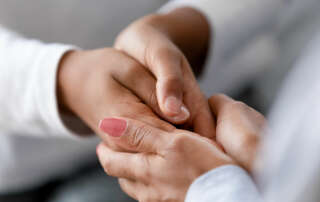 hands of a caregiver comforting another; suicide prevention concept