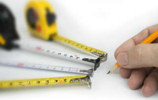 Four tape measures on white background with hand marking measurements