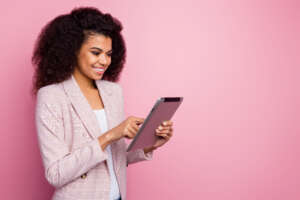 Smiling professional woman on pink background holds a tablet